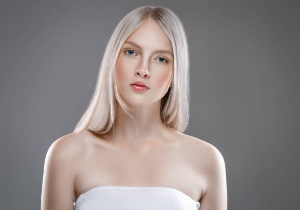 beautiful woman face portrait beauty skin care concept with long blonde hair. fashion beauty model with beautiful hairstyle over gray background - capelli ossigenati foto e immagini stock