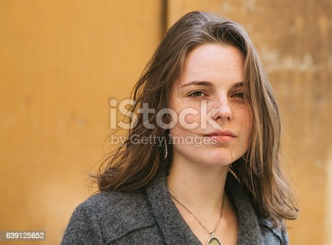 639939836 istock photo Beautiful woman face portrait freckles street city fashion 639125652
