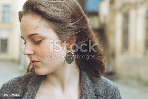 639939836 istock photo Beautiful woman face portrait freckles street city fashion 639125906