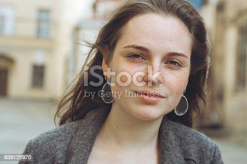 639939836 istock photo Beautiful woman face portrait freckles street city fashion 639125970
