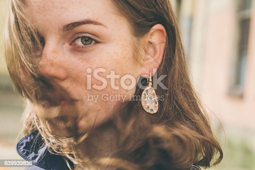 istock Beautiful woman face portrait freckles street city fashion 639939836