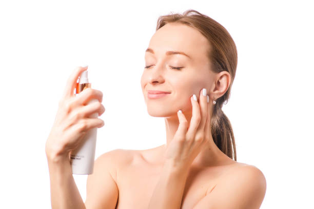 Beautiful woman face spray on face lotion cosmetology stock photo