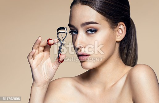 istock Beautiful woman face with clip for eyelashes 511792996