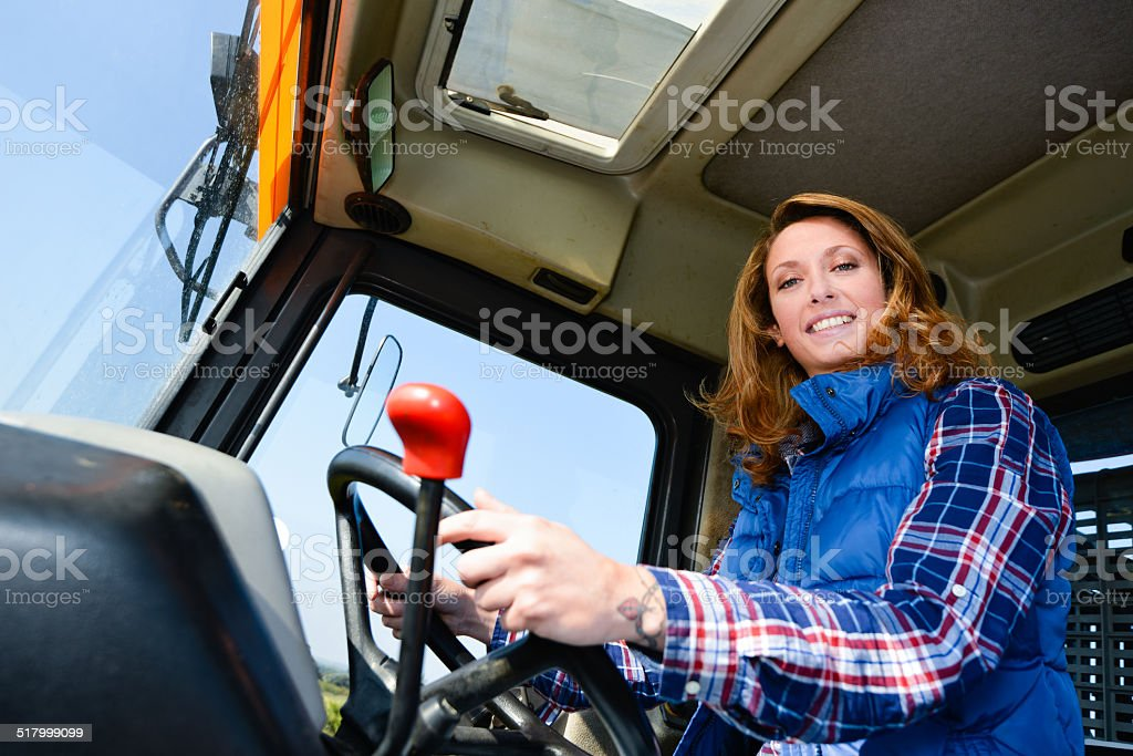 beautiful woman farmer driving tractor in fields during harvest countryside stock photo