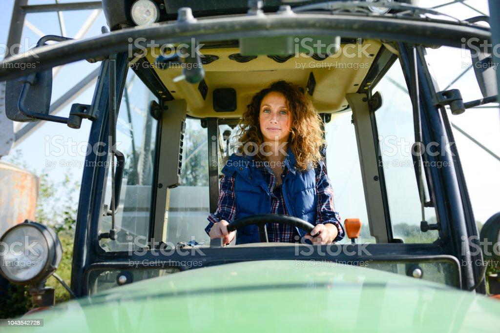 belle femme agricultrice en conduite tracteur dans le champ de la campagne - Photo