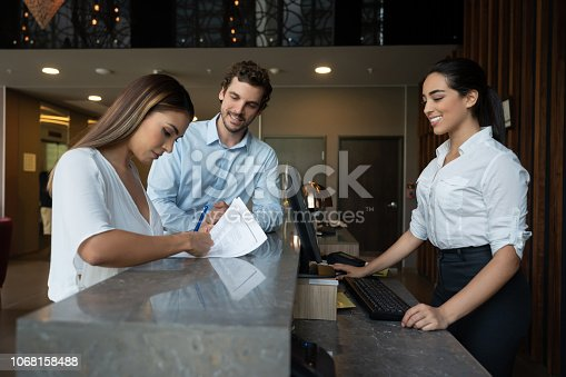 istock Beautiful woman filling form to check in to hotel with partner and friendly receptionist smiling while working on computer 1068158488