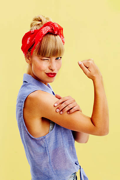 Beautiful woman flexing muscle Gorgeous strong woman winking at camera, portrait girl power stock pictures, royalty-free photos & images