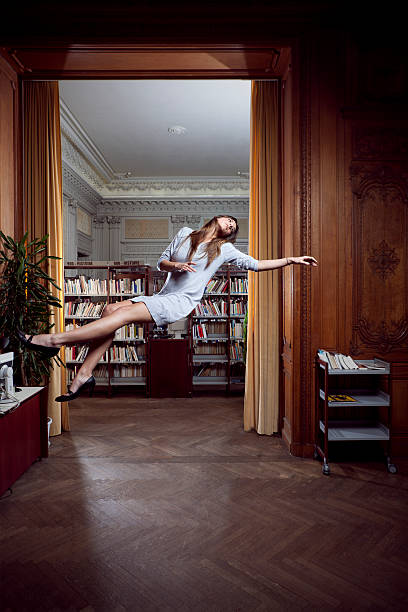 Beautiful woman floating in library concept stock photo