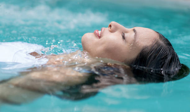 Beautiful woman floating in the swimming pool stock photo