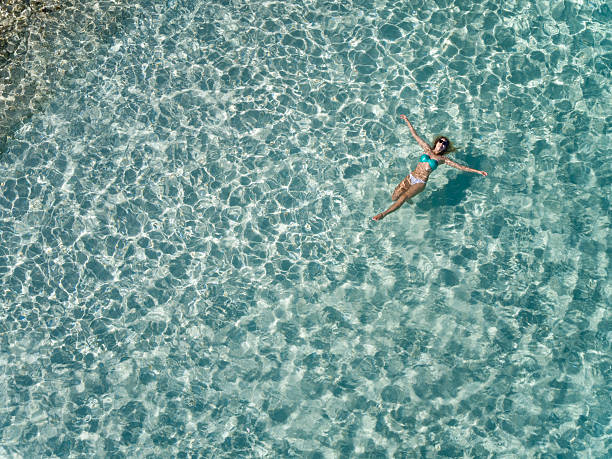 beautiful woman floating in tropical water stock photo