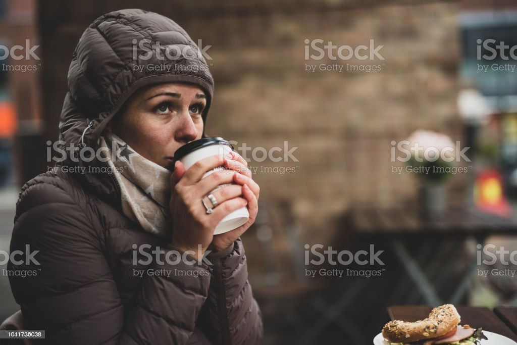 Female having breakfast outdoor at cold rainy day.