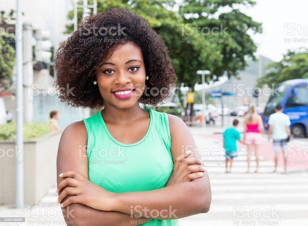 Linda mulher da África em uma camisa verde na cidade - foto de acervo