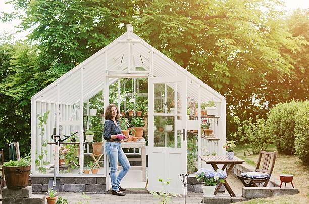 красивая женщина в саду на ее теплице - теплица стоковые фото и изображения