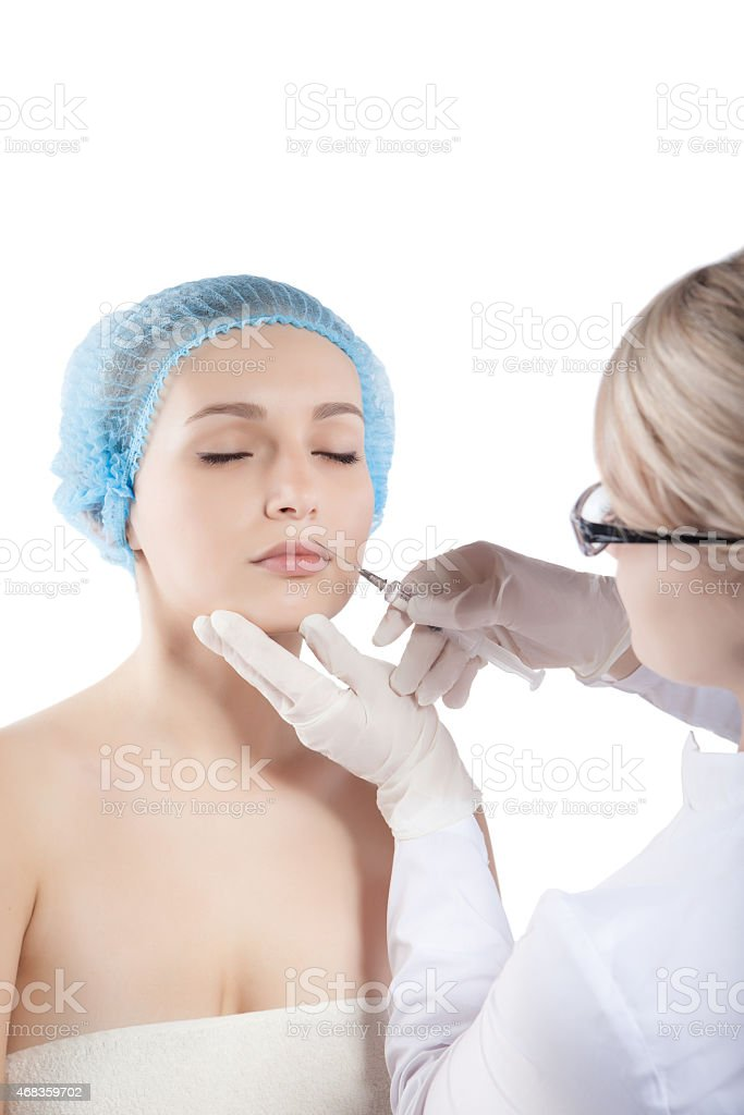 Beautiful woman gets an injection in her face royalty-free stock photo