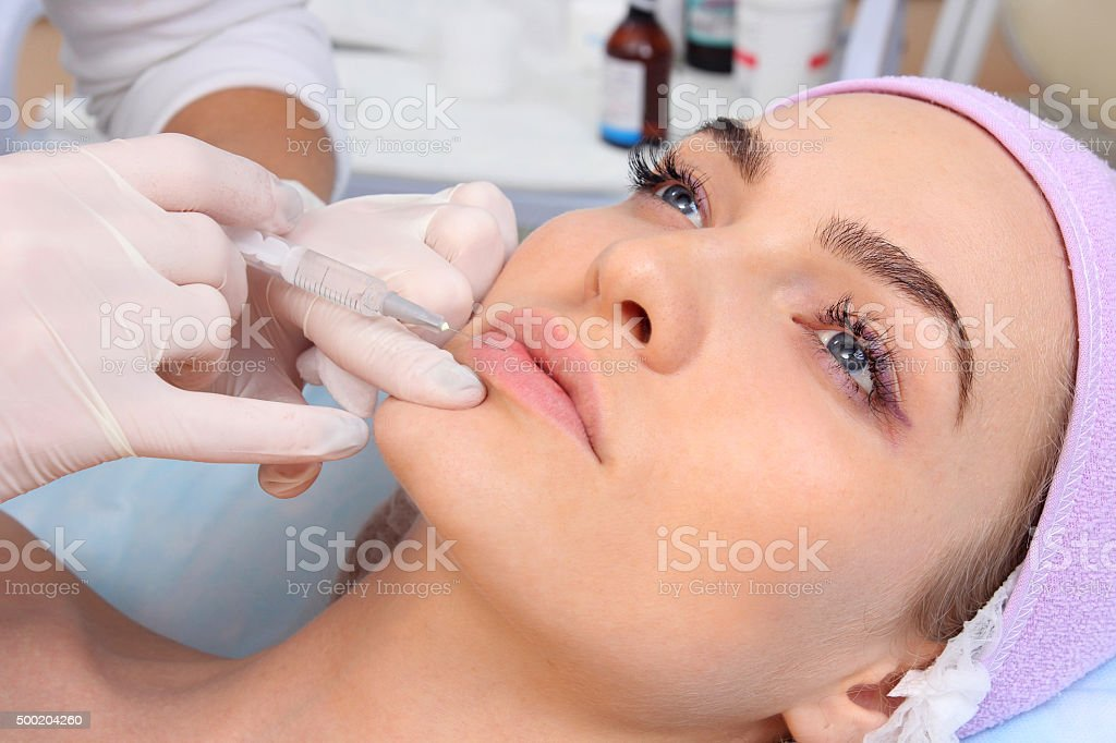 Beautiful woman gets an injection in her lips. stock photo