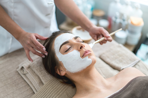 Portrait of a beautiful woman getting a facemask at the spa and taking care of her skin - beauty concepts