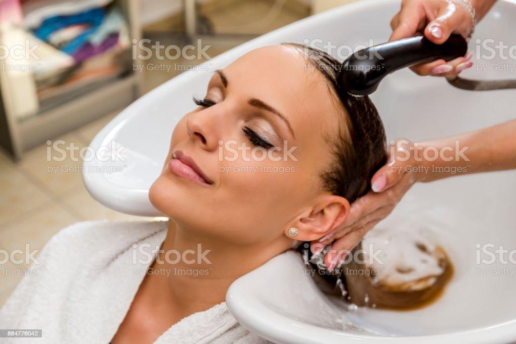 Beautiful woman getting hair wash in a hair salon stock photo
