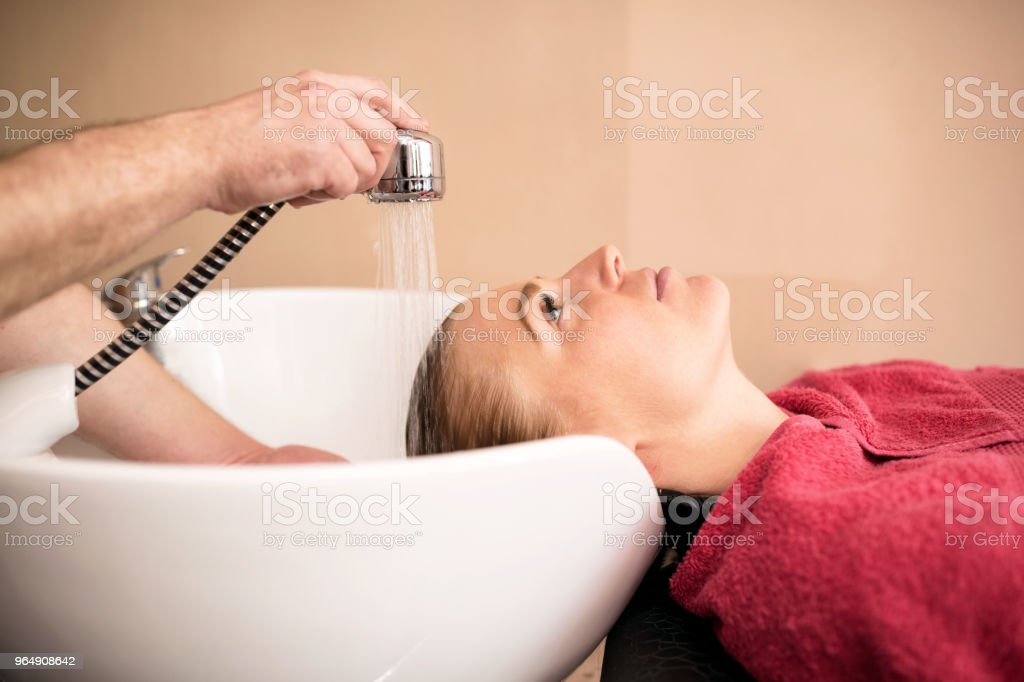 Beautiful woman getting hair wash in a hair salon royalty-free stock photo