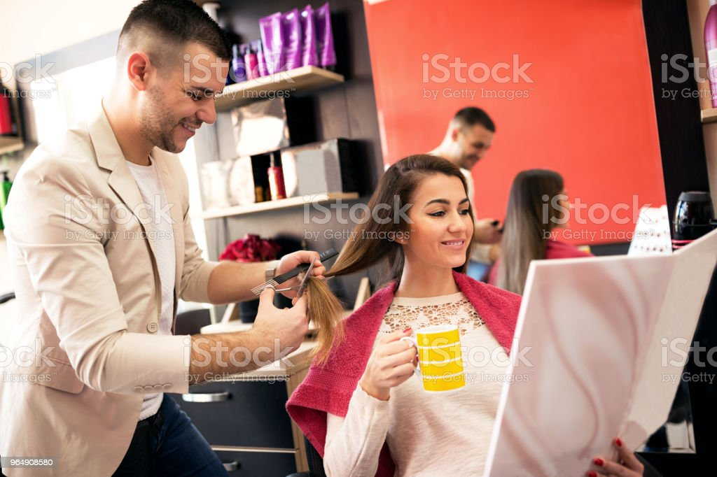 Beautiful woman getting haircut by hairdresser royalty-free stock photo