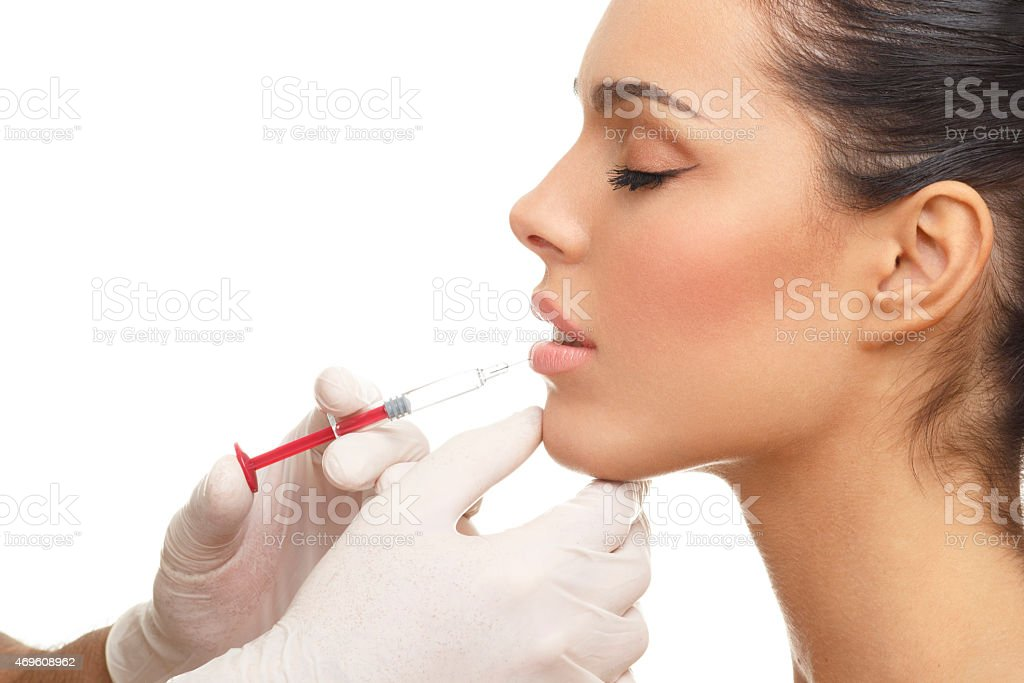 Beautiful woman getting lip injection stock photo
