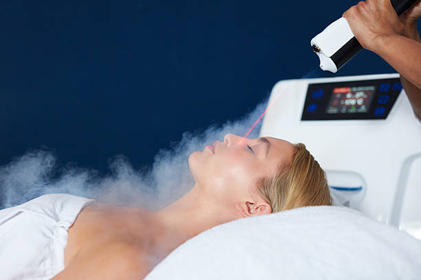 Beautiful woman getting local cryotherapy therapy Beautiful young woman getting local cryotherapy therapy in cosmetology clinic. Beautician applying cold nitrogen vapors to the face of woman. cryotherapy stock pictures, royalty-free photos & images