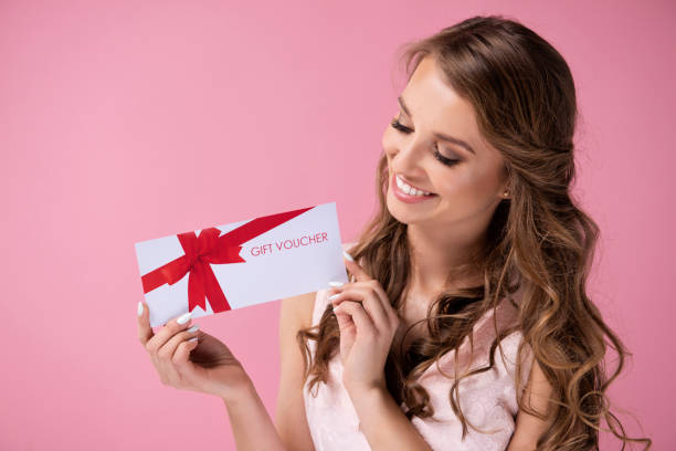 Beautiful woman giving a gift voucher stock photo