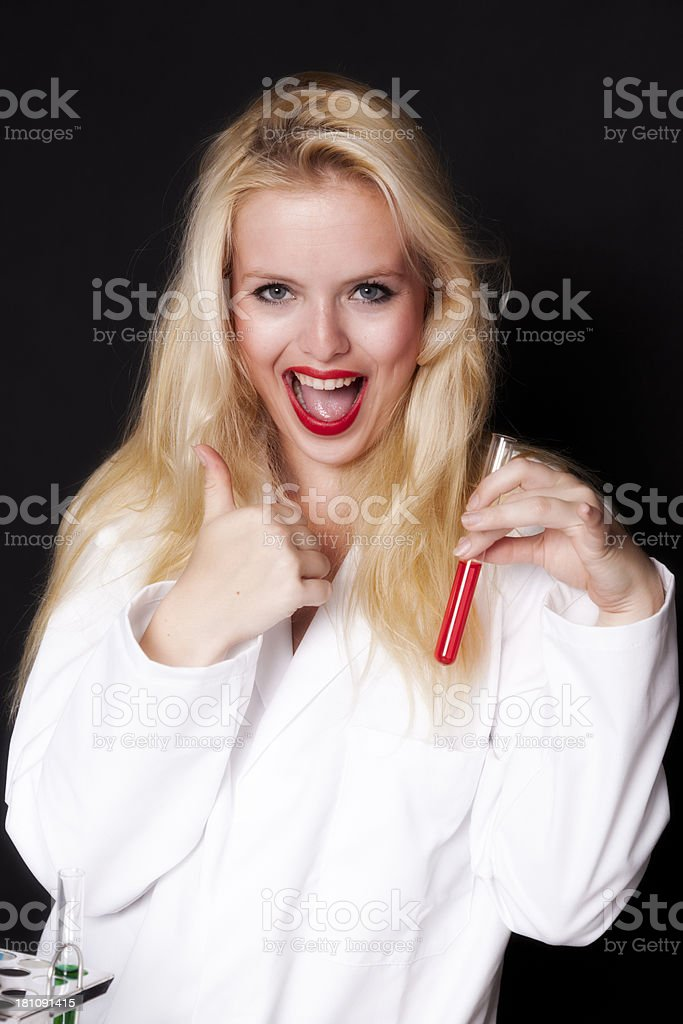 Beautiful woman giving thumbs up and holding test tube royalty-free stock photo