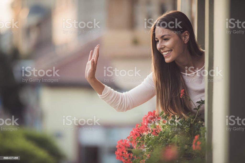 Beautiful woman greeting someone on the street from her house window beautiful woman greeting someone on the street from her house window royalty free stock m4hsunfo