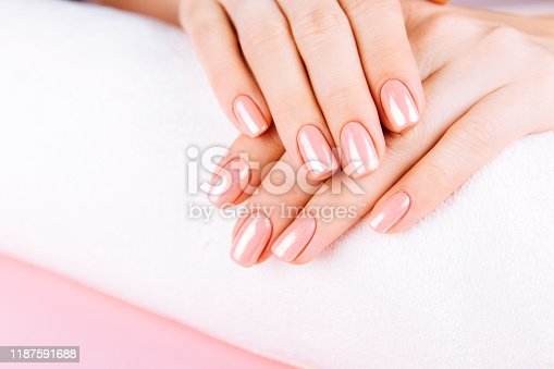 946930880istockphoto Beautiful Woman Hands . Spa and Manicure concept. Female hands with pink manicure. Soft skin skincare concept. Beauty nails. Over beige background. 1187591688