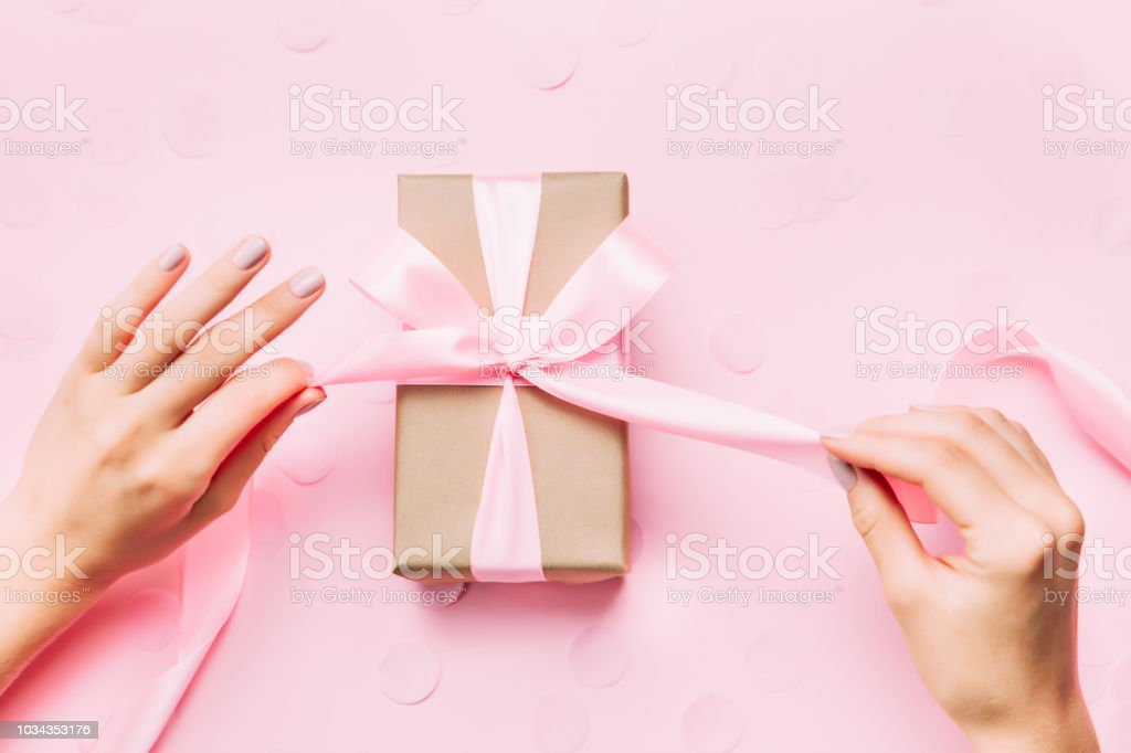 Beautiful woman hands with beautiful pastel manicure open gift box on...