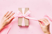 istock Beautiful woman hands with beautiful manicure open gift box. 1034353176