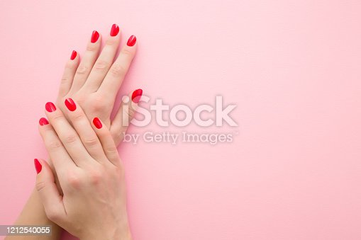 1147741037 istock photo Beautiful woman hands with red nails on light pink table background. Pastel color. Manicure beauty salon concept. Empty place for text or logo. Closeup. Top down view. 1212540055