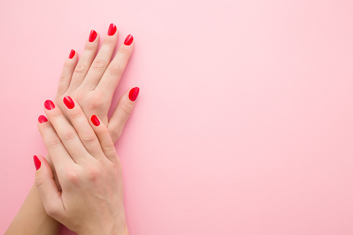 Beautiful woman hands with red nails on light pink table background. Pastel color. Manicure beauty salon concept. Empty place for text or logo. Closeup. Top down view.