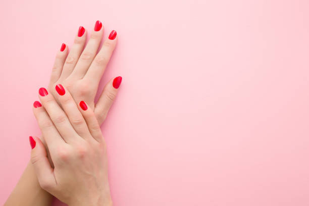 Beautiful woman hands with red nails on light pink table background. Pastel color. Manicure beauty salon concept. Empty place for text or logo. Closeup. Top down view. stock photo