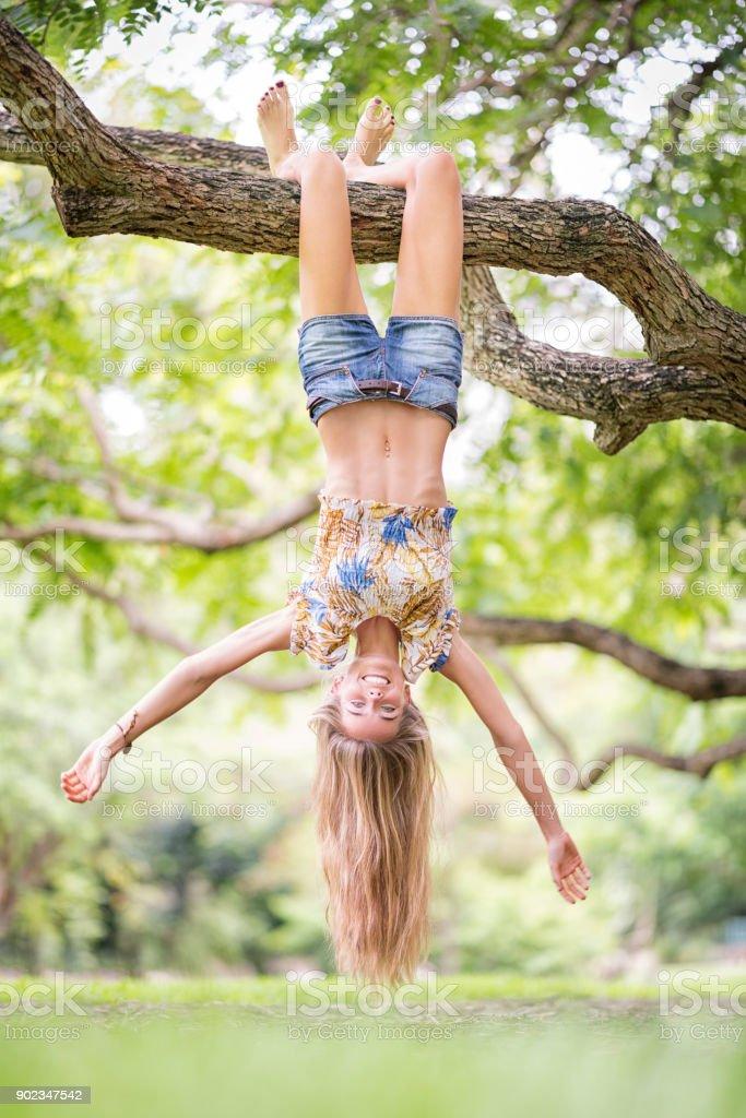 Beautiful Woman hanging upside down from a huge Tree Branch enjoying...