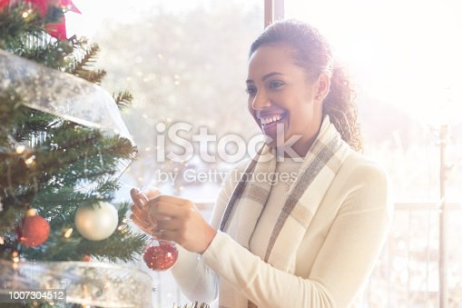 A smiling mid adult woman hangs an ornament on her Christmas tree at home.  There is a bright window behind her.