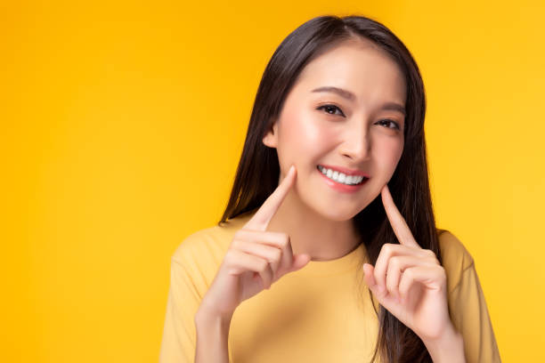 Beautiful woman has beautiful tooth, white teeth, nice tooth alignment. She get her teeth cleaned. Pretty girl show her teeth. copy space, yellow background stock photo