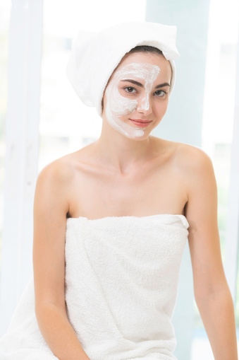 istock Beautiful woman having a facial treatment at spa. 963087544