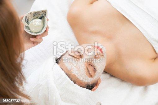 istock Beautiful woman having a facial treatment at spa. 963087732