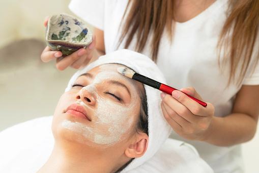 istock Beautiful woman having a facial treatment at spa. 963087736