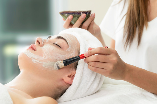 istock Beautiful woman having a facial treatment at spa. 982514036