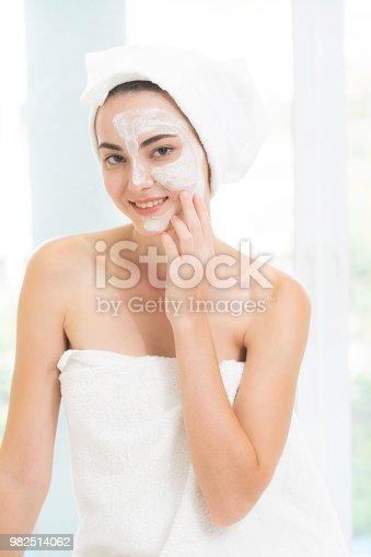 istock Beautiful woman having a facial treatment at spa. 982514062