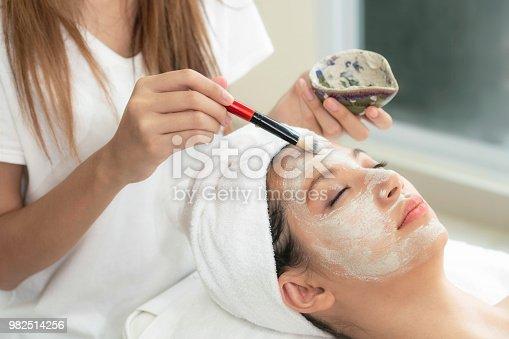 istock Beautiful woman having a facial treatment at spa. 982514256