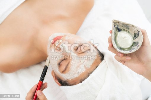 istock Beautiful woman having a facial treatment at spa. 982514288