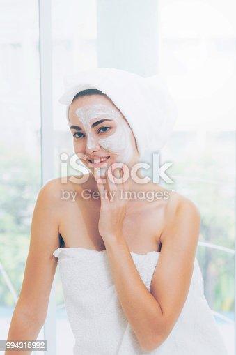 istock Beautiful woman having a facial treatment at spa. 994318992