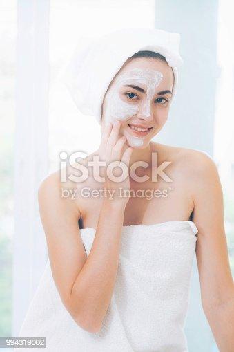 istock Beautiful woman having a facial treatment at spa. 994319002
