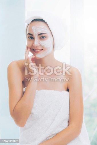 istock Beautiful woman having a facial treatment at spa. 994319028