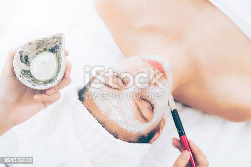istock Beautiful woman having a facial treatment at spa. 994319210