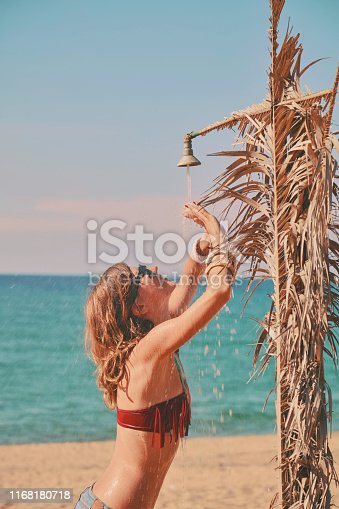 545091450istockphoto Beautiful woman having a shower on the tropical beach. Summer concept. 1168180718