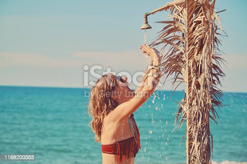 545091450istockphoto Beautiful woman having a shower on the tropical beach. Summer concept. 1168200353